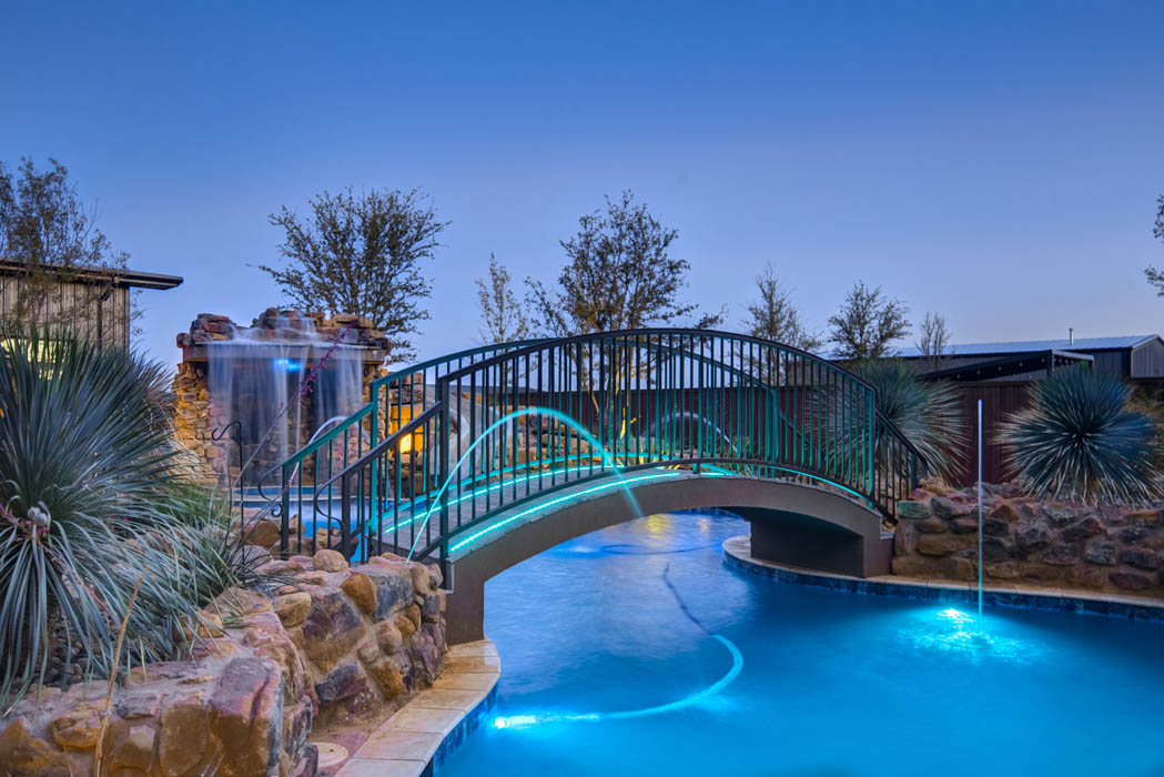 Bridge with evening lights, spanning custom swimming pool in custom-built home near Lubbock.